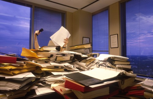 a businesswoman is hidden behind a huge pile of papers books files in corner office of large corporate firm. Image shot 2001. Exact date unknown.