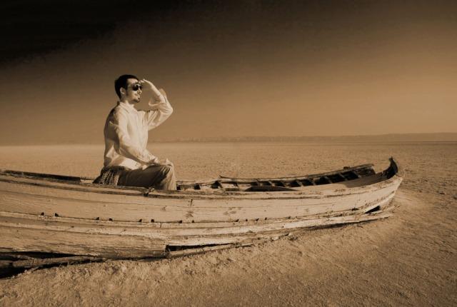 Young man in stranded boat rack in the desert