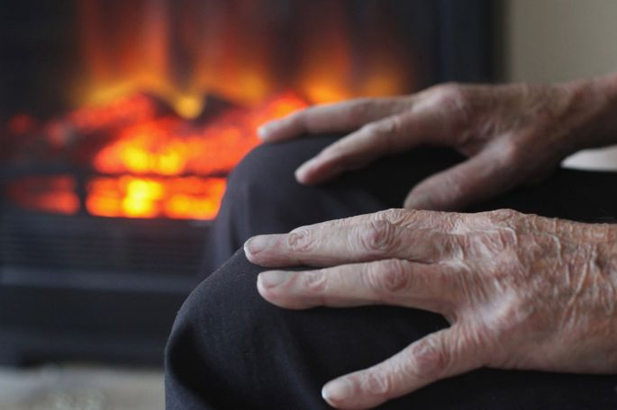 Elderly man warms himself in front of a fire